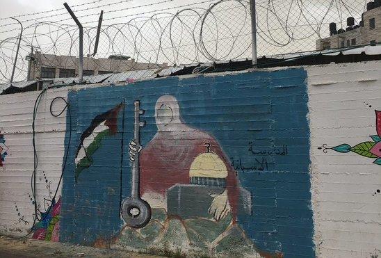 Peinture sur un mur barbelé à Ramallah en Cisjordanie représentant la mosquée et la clé de Jaffa, emblèmes palestiniens. (Crédit photo : A. Filatre)